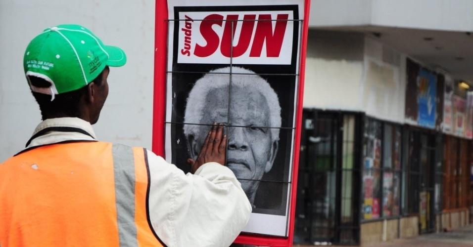 7.dez.2013 - Em Durban, na África do Sul, um homem coloca sua mão sobre foto do rosto do presidente Nelson Mandela, morto na quinta-feira (5). A briga pela herança do líder sul-africano já começou
