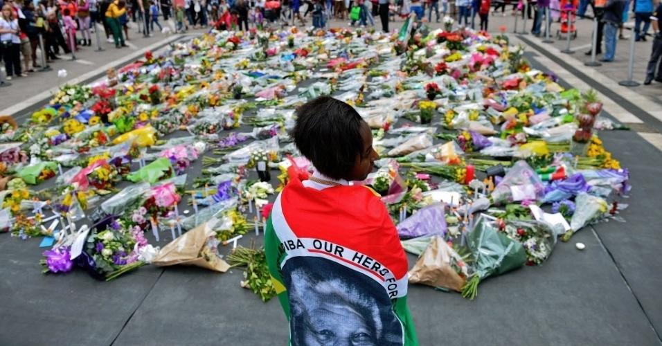 7.dez.2013 - Em luto, a garota Zamo Sibanyoni veste uma bandeira com a imagem de Nelson Mandela, morto na quinta-feira (5), enquanto encara flores depositadas próximo à estátua do líder sul-africano. A briga pela herança de Mandela já começou na África do Sul
