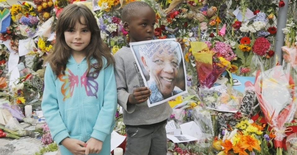 7.dez.2013 - Um menino e uma menina posam em frente a uma parede de flores em frente à casa de Nelson Mandela em Joanesburgo, África do Sul. As flores sã uma homenagem de milhares de pessoas em luto pela morte do líder, morto na quinta-feira (5). A briga por sua herança já começou na África do Sul