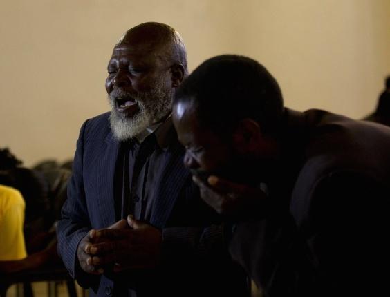 8.dez.2013 - O Reverendo Lucas Sontaga, à esquerda, faz uma prece em homenagem ao ex-presidente sul-africano Nelson Mandela, em Mvezu, onde ele nasceu. O líder na luta anti-apartheid morreu na quinta-feira (5), em Johannesburgo