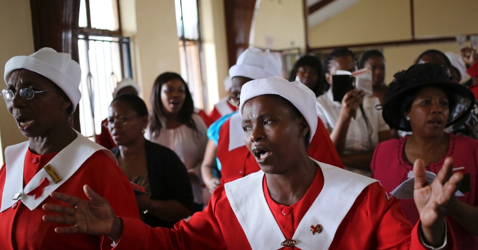 Mulheres rezam por Nelson Mandela em igreja na África do Sul, neste domingo (8). O ex-presidente  sul-africano morreu na última quinta-feira (5) aos 95 anos