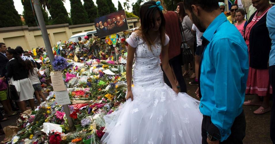 9.dez.2013 - Casal recém-casado presta homenagem em frente à casa onde viveu ex-presidente sul-africano Nelson Mandela, em Johanesburgo
