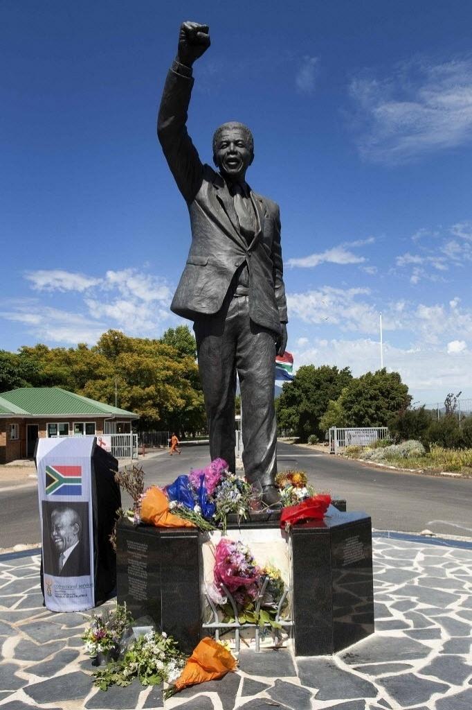 9.dez.2013 - Flores deixadas aos pés da estátua de Nelson Mandela, na entrada da prisão onde o líder sul-africano cumpriu os três últimos anos de sua pena, na Cidade do Cabo (África do Sul)