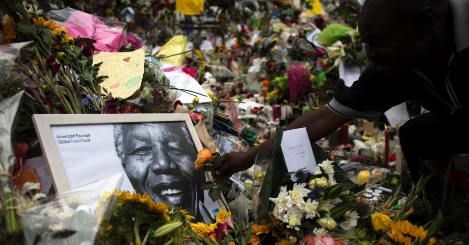 9.dez.2013 - Homem coloca flores em frente à casa de Nelson Mandela, em Johanesburgo, África do Sul