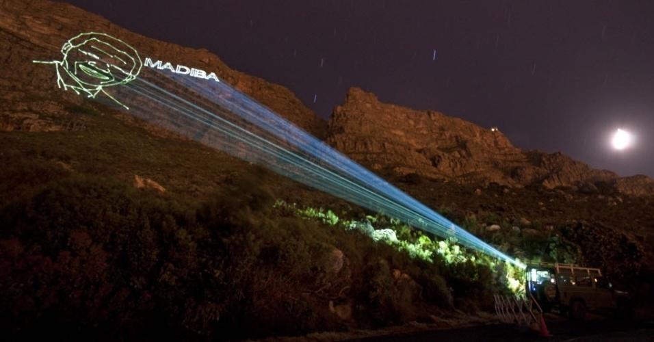 9.dez.2013 - Imagem do rosto de Nelson Mandela, com o seu apelido, Madiba, é projetada na montanha da Mesa, na cidade do Cabo. A África do Sul começou a se preparar para receber, na próxima semana, os vários líderes mundiais que irão ao país para assistir ao funeral de Estado do ex-presidente, que acontecerá no dia 15 de dezembro. Mandela morreu na última quinta (5), aos 95 anos