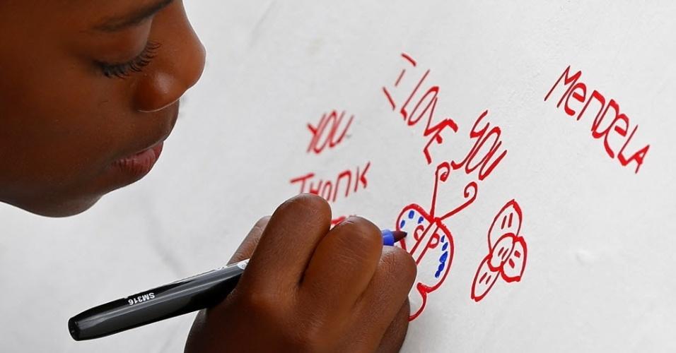 """9.dez.2013 - Mpho Xaba, 8, deixa mensagem em muro perto da casa em que o ex-presidente da África do Sul Nelson Mandela viveu em Soweto, nesta segunda-feira (9). A organização ativista Avaaz ergueu no local um muro de """"gratidão"""" e """"amor"""" mundial em memória de Nelson Mandela, para ser coberto de mensagens de admiradores de todo o mundo"""