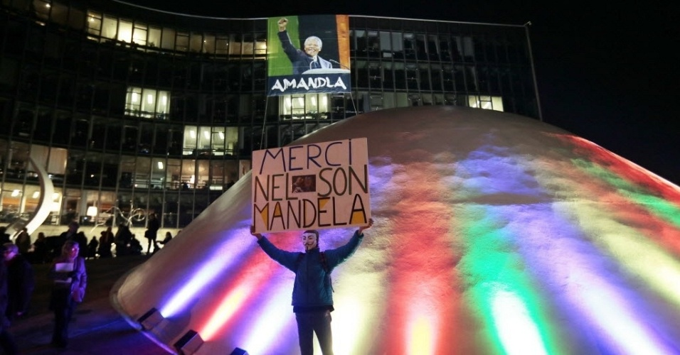 9.dez.2013 - Pessoa mascarada ergue cartaz em homenagem a Nelson Mandela em frente à sede do Partido Comunista Francês, em Paris