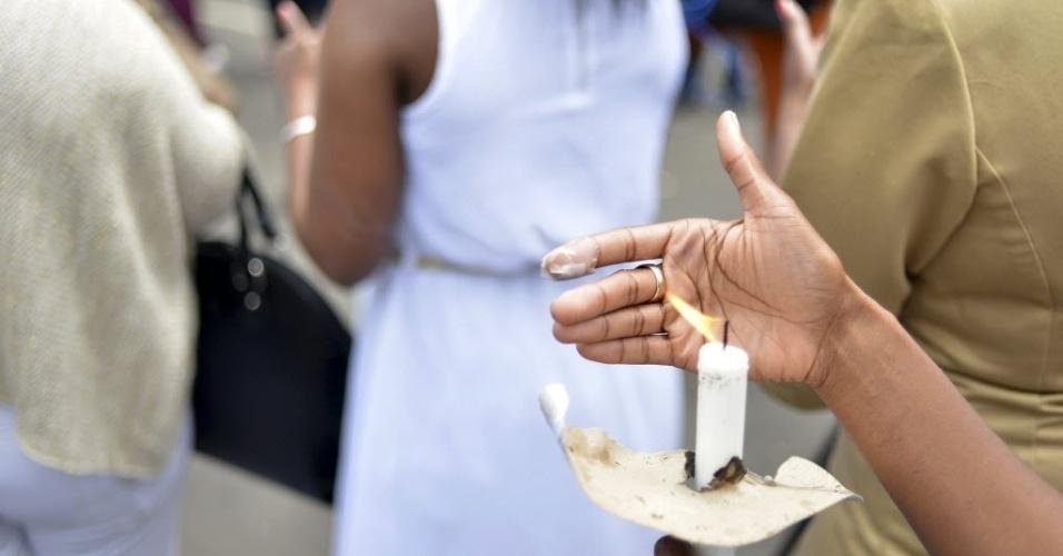 9.dez.2013 - Pessoas seguram vela em homenagem a Nelson Mandela em Johannesburgo nesta segunda-feira (9). Centenas de sul-africanos continuam peregrinando ao local, onde deixam suas mensagens de reconhecimento a Mandela e cantam e dançam lembrando seu legado