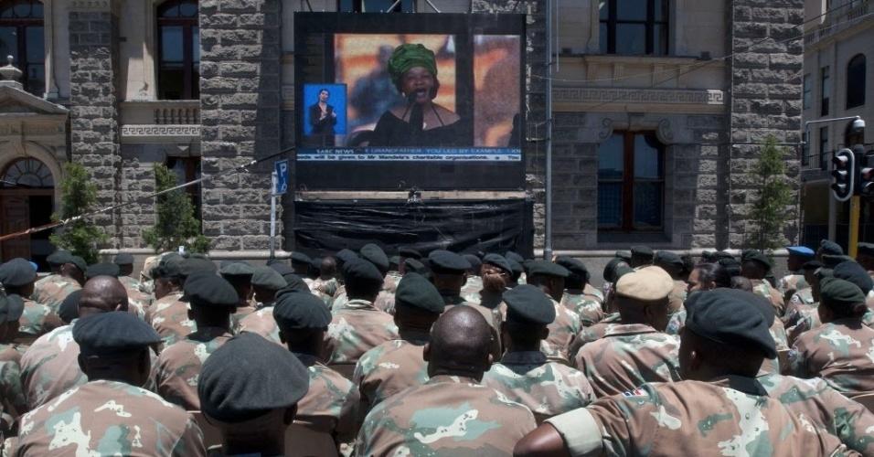10.dez.2013 - Membros da Força de Defesa Nacional da África do Sul assistem ao funeral do ex-presidente  Nelson Mandela, em telões no centro da cidade de Cape Town