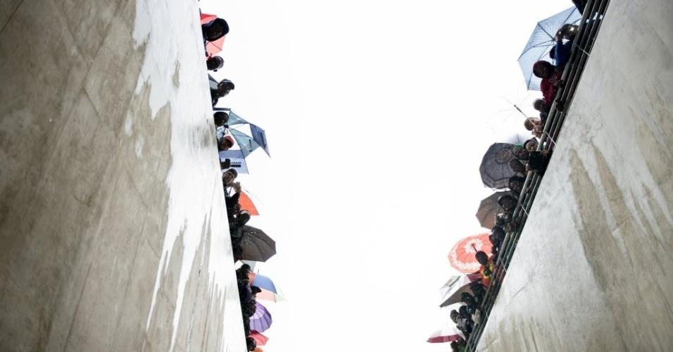 10.dez.2013 - Pessoas aguardam chegada do presidente dos Estados Unidos, Barack Obama, a cerimônia de homenagem a Nelson Mandela no estádio Soccer City, em Johannesburgo