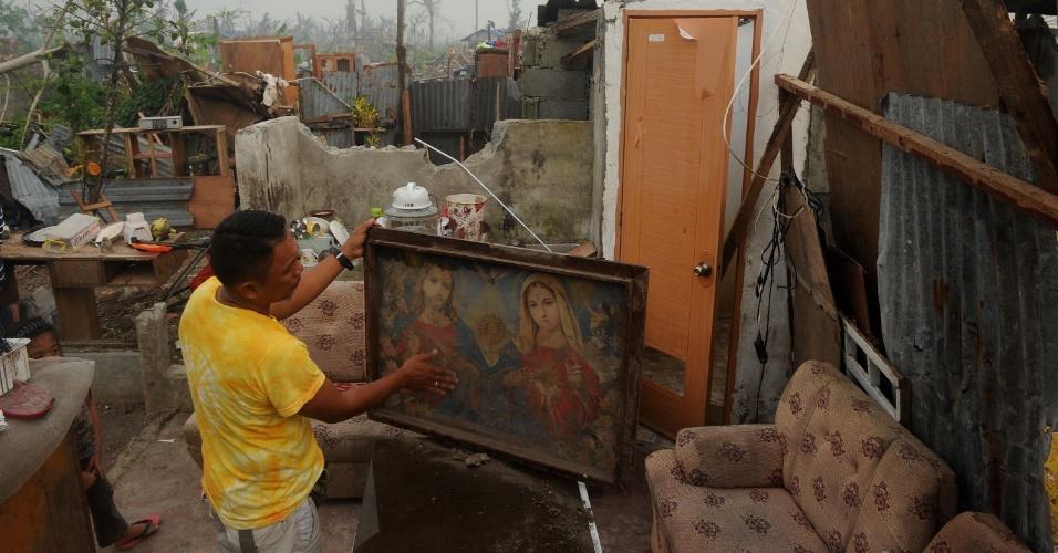 10.dez.2013 - Sobrevivente do tufão que devastou as Filipinas há um mês, encontra quadro com imagem de Jesus e da Virgem Maria por entre escombros da casa em que morava em Tacloban e que foi destruída pela força dos ventos