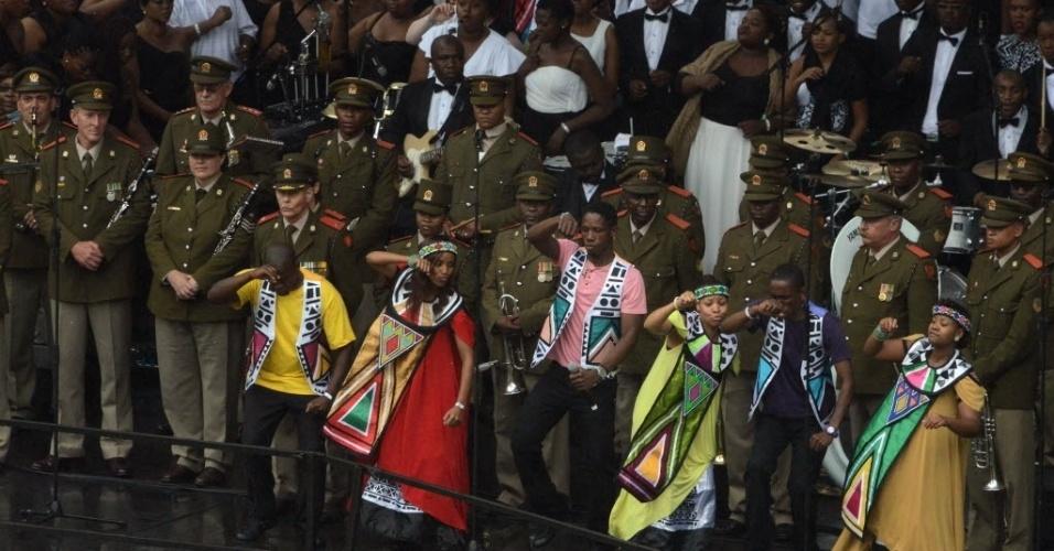 10.dez.2013 - Sul-africanos cantam e dançam em frente a soldados durante funeral de Nelson Mandela no estádio Soccer City- no bairro de Soweto, em Johannesburgo, África do Sul