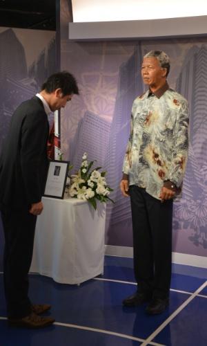 10.dez.2013 - Visitante do museu Madame Tussauds, em Tóquio (Japão), reverencia escultura de cera do ex-presidente sul-africano e Nobel da Paz Nelson Mandela, morto no último dia 5, aos 95 anos, em Johannesburgo (África do Sul)