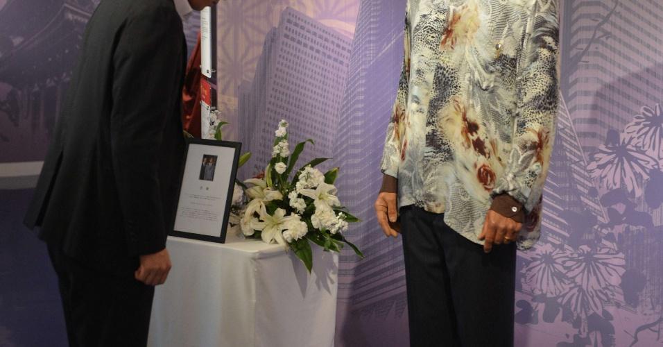10.dez.2013 - Visitante do museu Madame Tussauds, em Tóquio (Japão), reverencia escultura de cera do ex-presidente sul-africano e Nobel da Paz Nelson Mandela, morto no último dia 5, aos 95 anos, em Johanesburgo (África do Sul)
