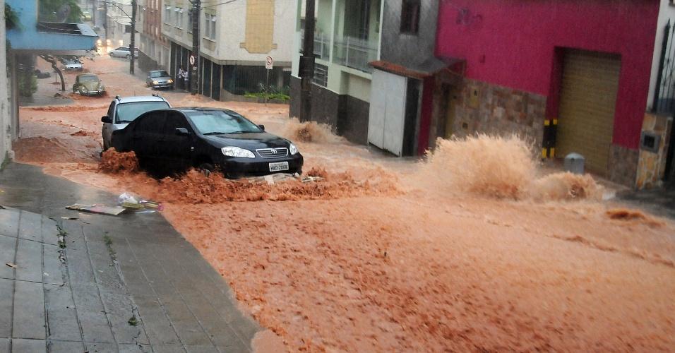 11.dez.2013 - A enxurrada provocada pelas fortes chuvas na cidade de Juiz de Fora (MG) arrastou carros na rua Santos Dumont, no bairro Granbey, nesta quarta-feira