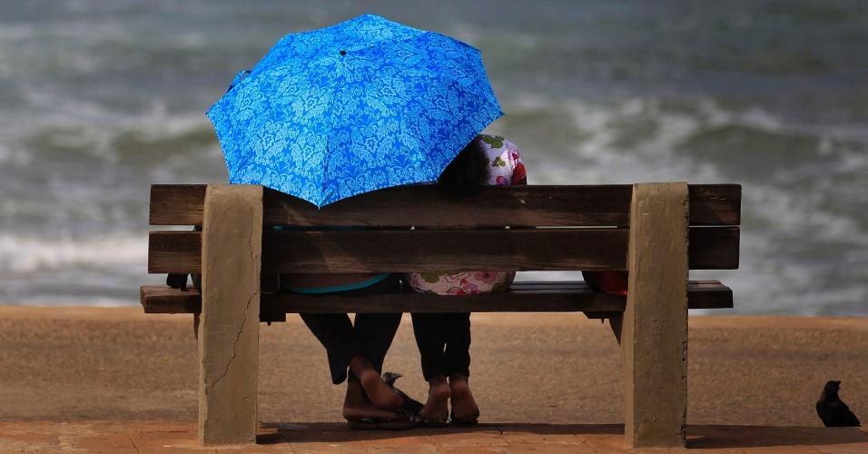 12.dez.2013 - Casal se protege do sol enquanto observa o mar, nesta quinta-feira (12), em Colombo, Sri Lanka