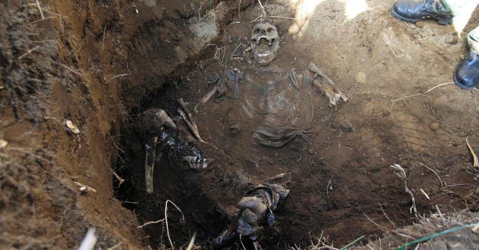 12.dez.2013 - Médico forense examina esqueleto encontrado em uma vala, nesta quinta-feira (12), em Lourdes, El Salvador. Especialistas acreditam que são os restos mortais de 24 pessoas desaparecidas e afirmam que mais corpos podem estar enterrados em uma montanha no local