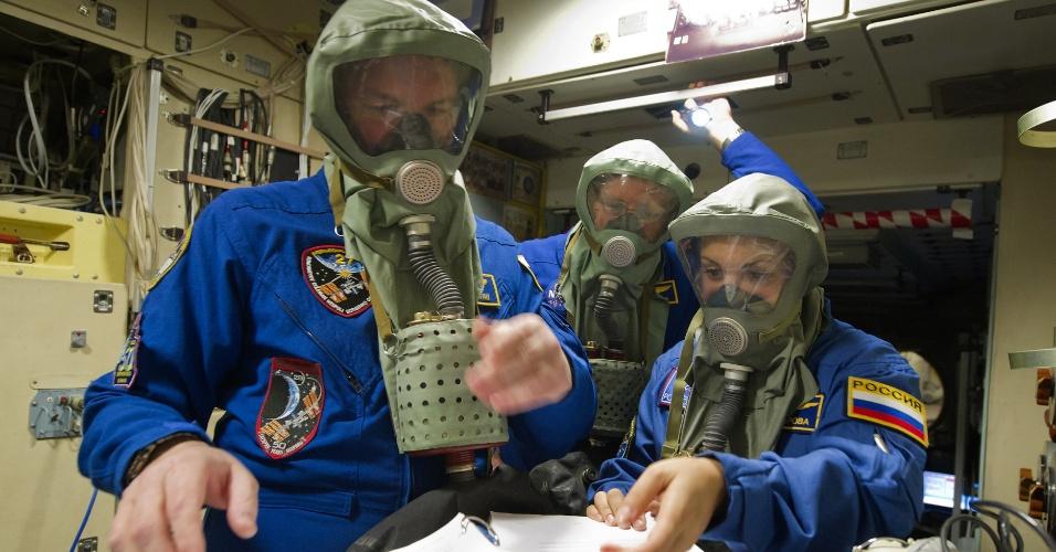 11.dez.2013 - Os cosmonautas russos Elena Serova (à dir.) e Alexandr Samokutyaev (à esq.), juntamente com o astronauta norte-americano Barry Wilmore, participam de sessão de treinamento com máscaras de gás nesta quarta-feira (11) no Centro de Treinamento dos Cosmonautas Gagarin, em Star City, nos arredores de Moscou (Rússia). Os três irão viajar para a Estação Espacial Internacional (ISS, na sigla em inglês) partindo do cosmódromo de Baikonur (Cazaquistão) em setembro de 2014