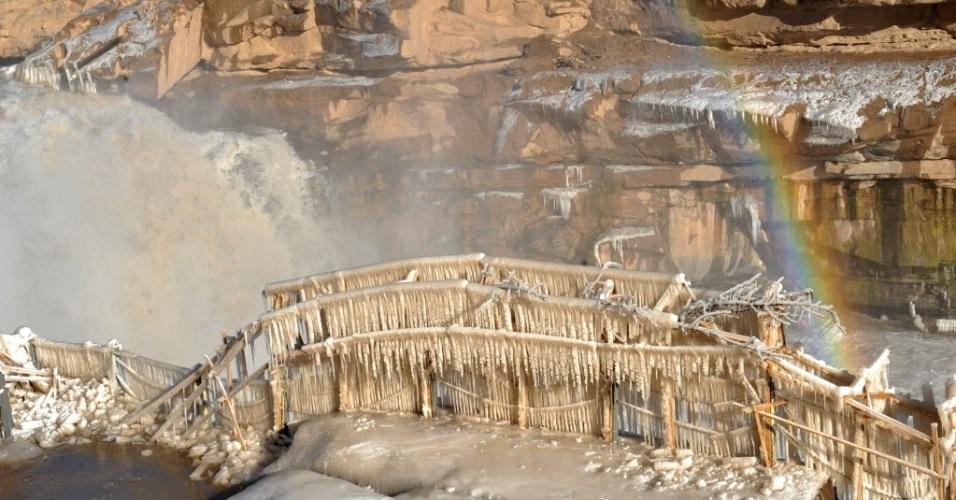 12.dez.2013 - Cachoeira congelada, com arco-íris ao fundo, no rio Amarelo, na província de Shaanxi, no noroeste da China, nesta quinta-feira (12). Pela primeira vez, o local está aberto para visitação no inverno