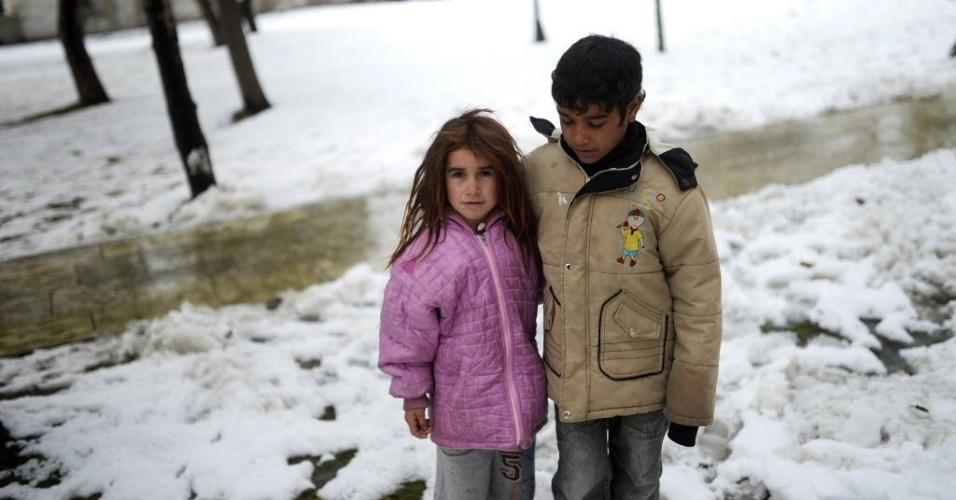 12.dez.2013 - Crianças sírias refugiadas na Turquia andam na neve nesta quinta-feira (12) em Istambul. O frio rigoroso e a escassez de suprimentos aumentam as dificuldades dos refugiados da guerra civil da Síria. A tempestade de neve forçou o fechamento de estradas e escolas e cobriu campos de refugiados na região
