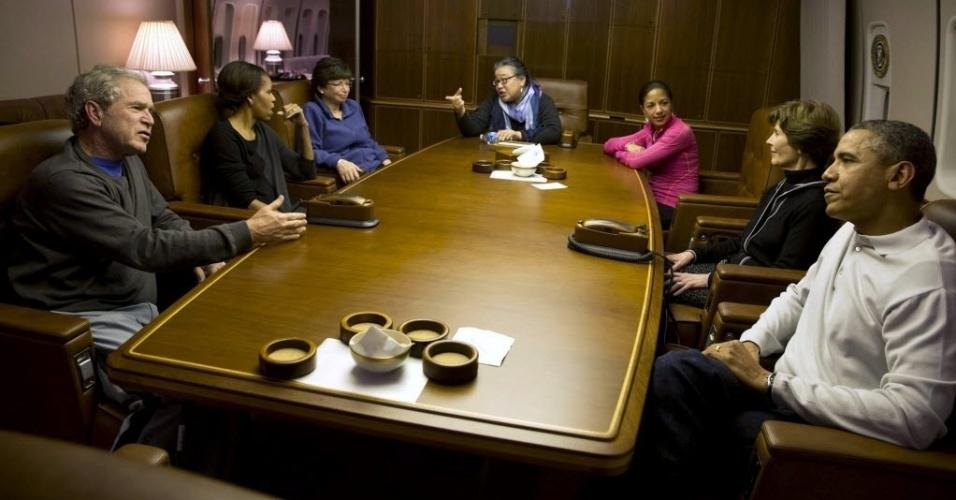 12.dez.2013 - Em foto divulgada pela Casa Branca nesta quinta-feira (12), o presidente dos Estados Unidos, o ex-presidente dos EUA, George W. Bush, mostra fotos de suas pinturas para (da esq. para a dir.) a primeira dama Michelle Obama, a ex-secretária de Estado Hillary Clinton, as conselheiras Valerie Jarrett e Susan Rice, o fiscal-geral Eric Holder e Laura Bush, mulher del ex-mandatário, no avião presidencial Air Force One a caminho de Johannesburgo, na África do Sul, onde participaram do funeral de Nelson Mandela na última terça (10)