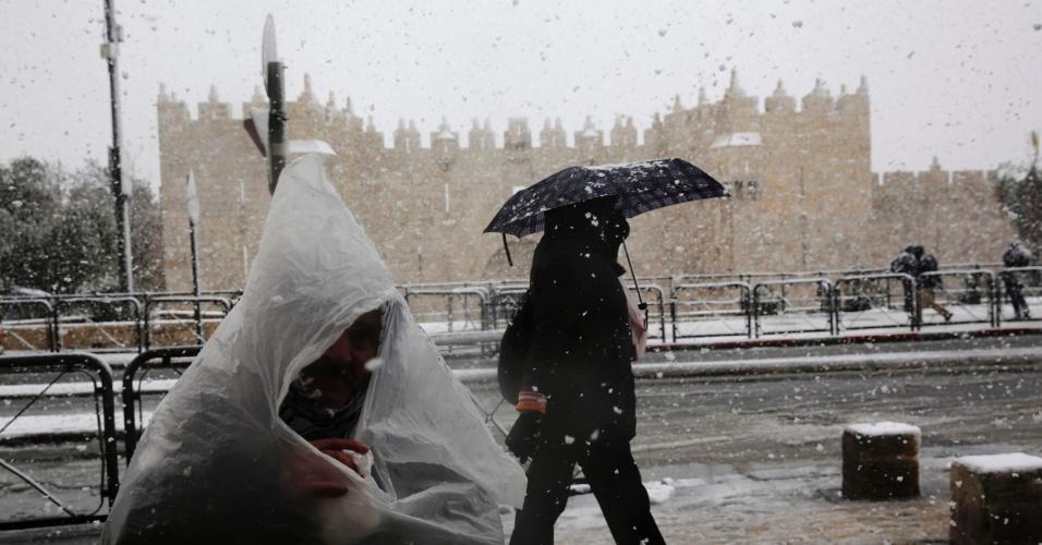 12.dez.2013 - Homem se protege da neve usando um saco plástico, nesta quinta-feira (12), em Jerusalém, Israel