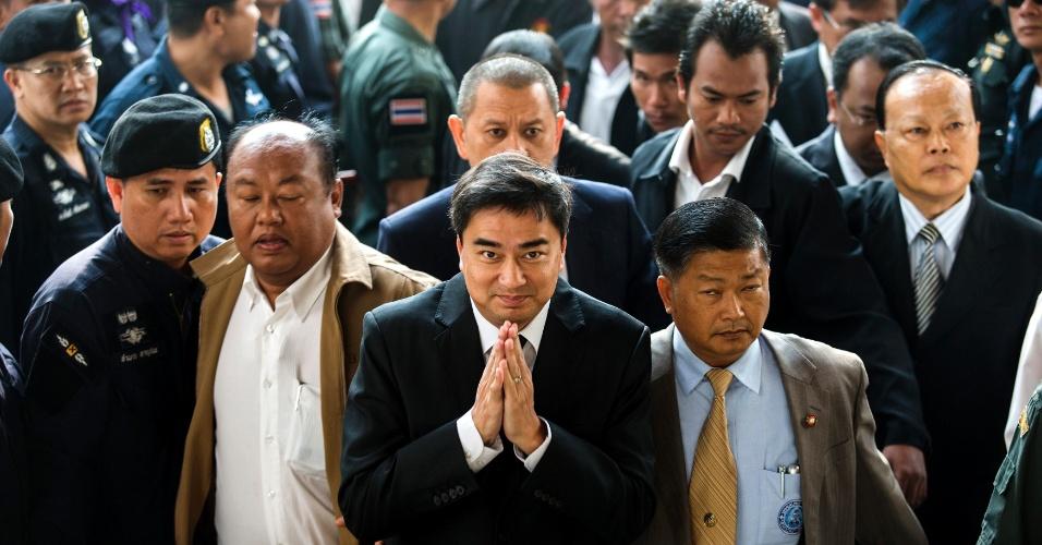 12.dez.2013 - Líder do Partido Democrata da Tailândia e ex-primeiro-ministro do país, Abhisit Vejjajiva (ao centro), gesticula nesta quinta-feira (12) após chegar ao tribunal penal de Bancoc. Abhisit é acusado de assassinato por causa da repressão militar que deixou mais de 90 manifestantes mortos no país em 2010