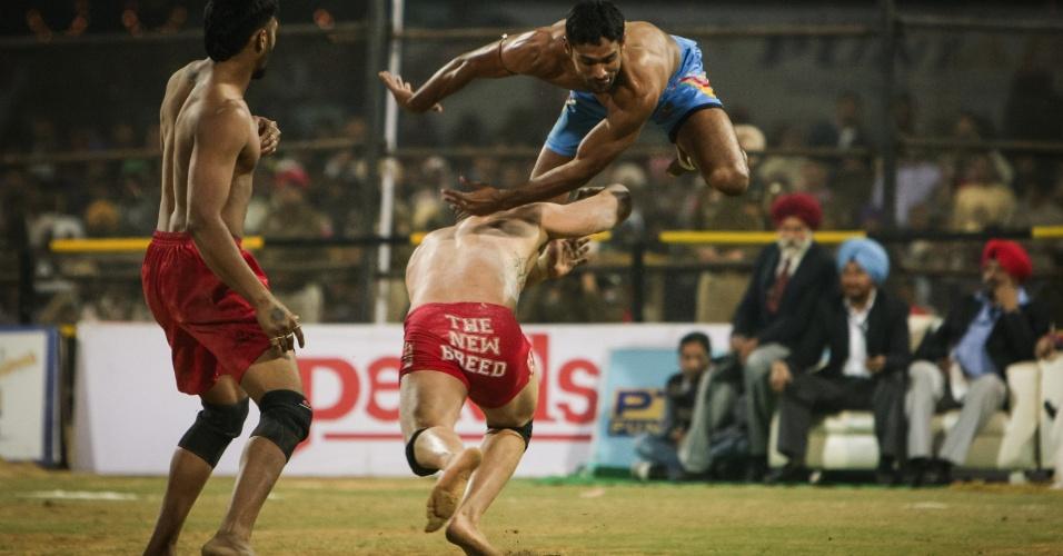 12.dez.2013 - Lutadores dos Estados Unidos e do Paquistão disputam partida de kabaddi, luta marcial tracional indiana, nesta quinta-feira (12), em Bathinda, na Índia