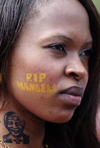 12.dez.2013 - Mulher exibe tatuagem feita com tinta removível com o rosto e o nome de Mandela durante velório do líder sul-africano em Pretória, na África do Sul, nesta quinta-feira (12)