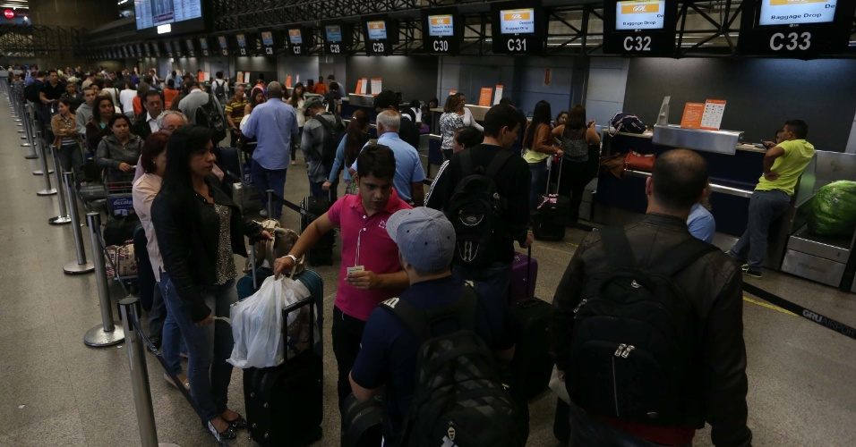 12.dez.2013 - Passageiros aguardam em fila a realização do check-in, nesta quinta-feira (12), no Aeroporto Internacional de Cumbica, em Guarulhos (SP). A implantação de um novo sistema de navegação aérea atrasou em 45 minutos a decolagem de aviões nos aeroportos de todo o Brasil. Nenhum avião decolou entre 23h45 de ontem (11) e 0h30 de hoje