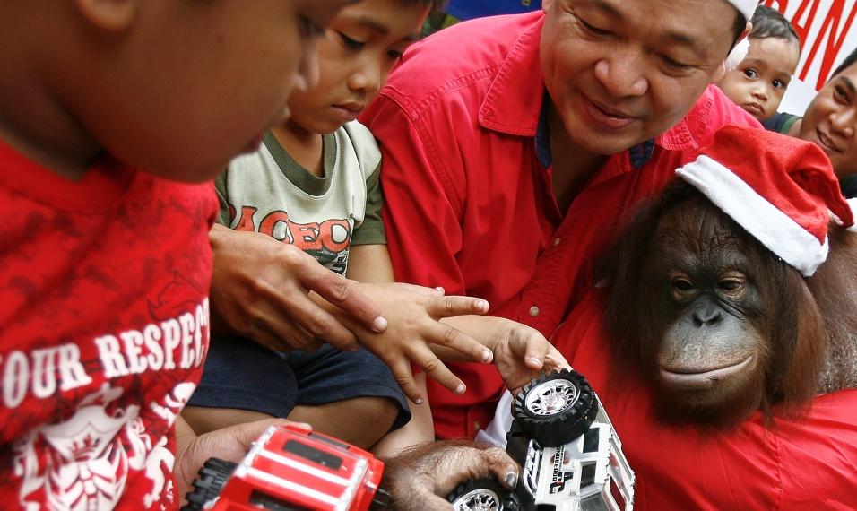 12.dez.2013 - Proprietário de zoológico Manny Tiangco e um orangotango vestido de Papai Noel dão presentes a crianças durante atividade natalina no Zoológico de Malabon (Filipinas)
