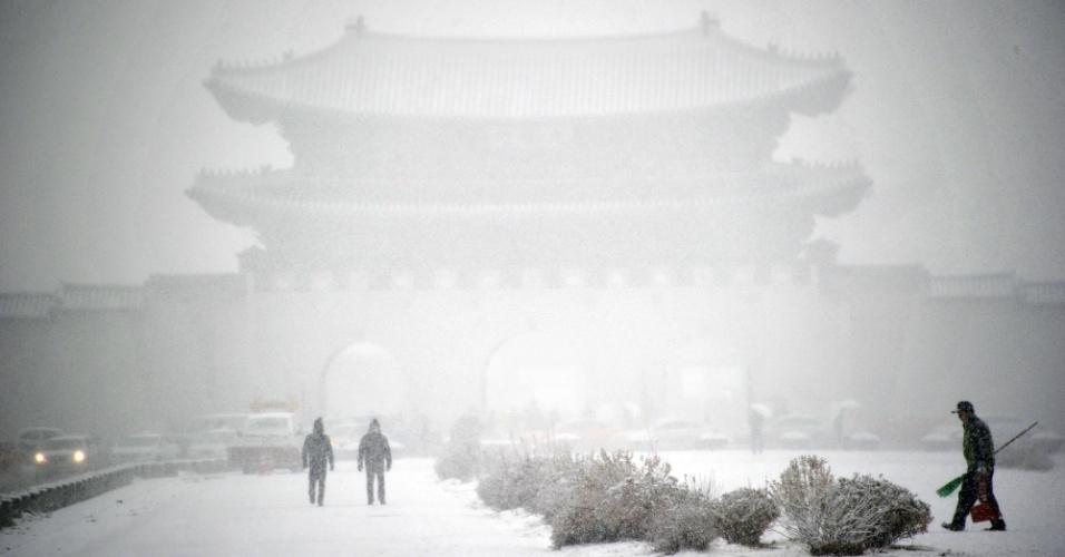 12.dez.2013 - Sul-coreanos andam em rua coberta de neve em Seul. A cidade emitiu alerta de nevasca, e a temperatura caiu abaixo de 0ºC