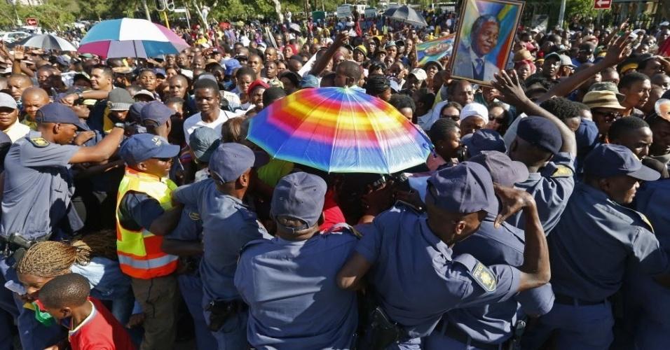 13.dez.2013 - Policiais sul-africanos tentam conter multidão que força as barreiras para se despedir de Nelson Mandela, em Pretória, no última dia de velório do ex-presidente. O enterro será no domingo (15)