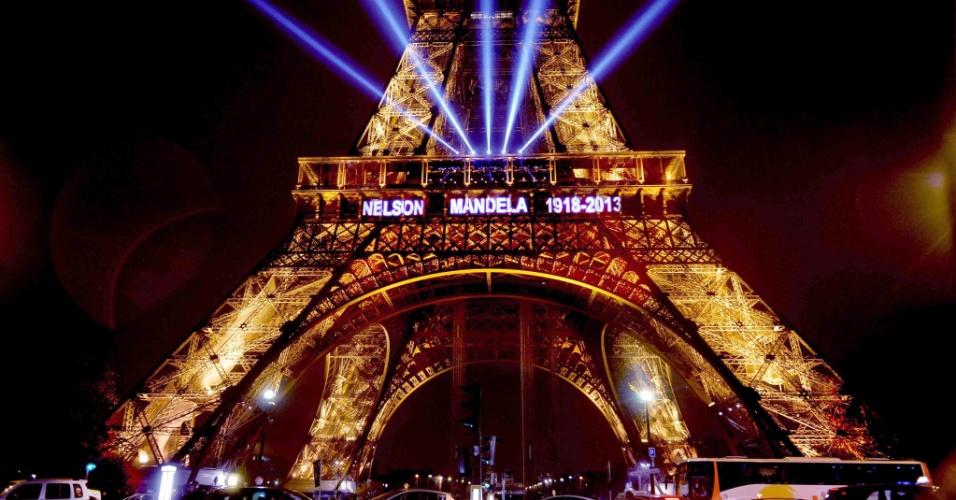 13.dez.2013 - Torre Eiffel, em Paris, ganha iluminação especial em homenagem ao ex-presidente sul-africano Nelson Mandela, que será enterrado no domingo (15)