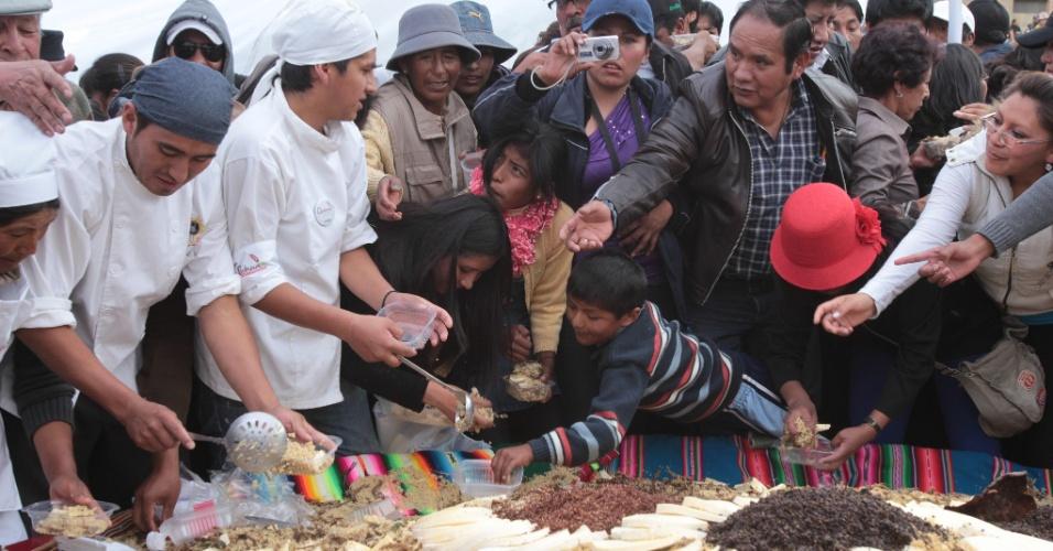14.dez.2013 - Bolivianos servem um prato típico do país chamado ''pisara'' em tamanho gigante, durante um festival em Oruro. O prato, feito com quinoa e carne de lhama, foi preparado para celebrar o fim do Ano Internacional da Quinoa, criado pela ONU (Organização das Nações Unidas)