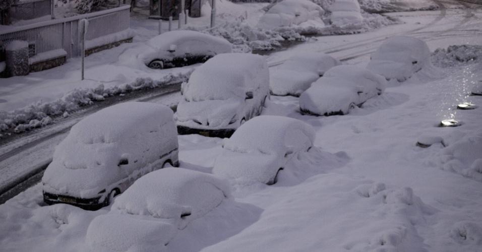 14.dez.2013 - Carros cobertos de neve são abandonados na beira da estrada durante uma nevasca em Jerusalém. Relatos indicam que cerca de 40 mil moradores da cidade estão sem eletricidade após a tempestade de neve