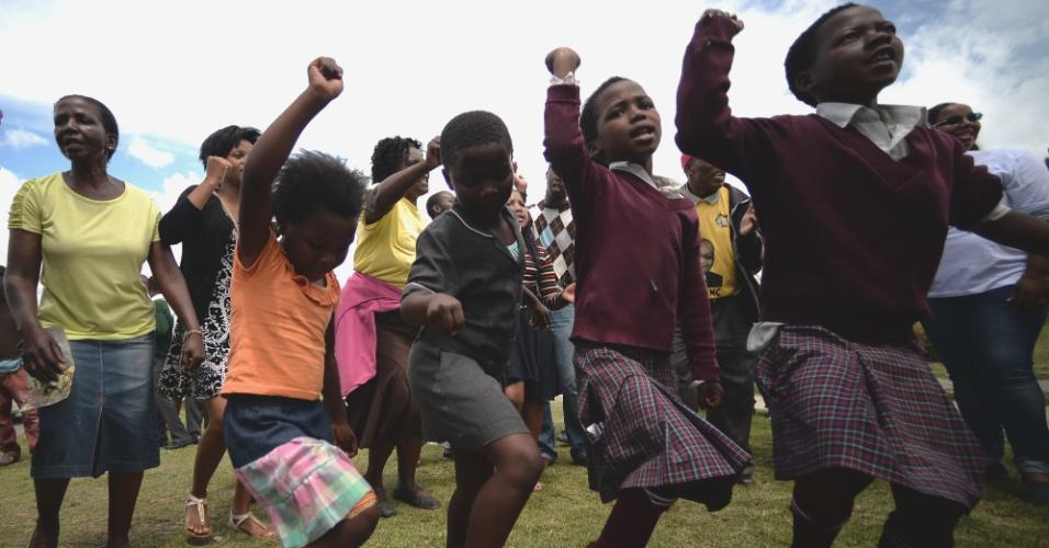 14.dez.2013 - Crianças dançam enquanto esperam o comboio que transporta o caixão de Nelson Mandela passar por Mthatha, no caminho para Qunu, onde o ex-presidente da África do Sul será enterrado