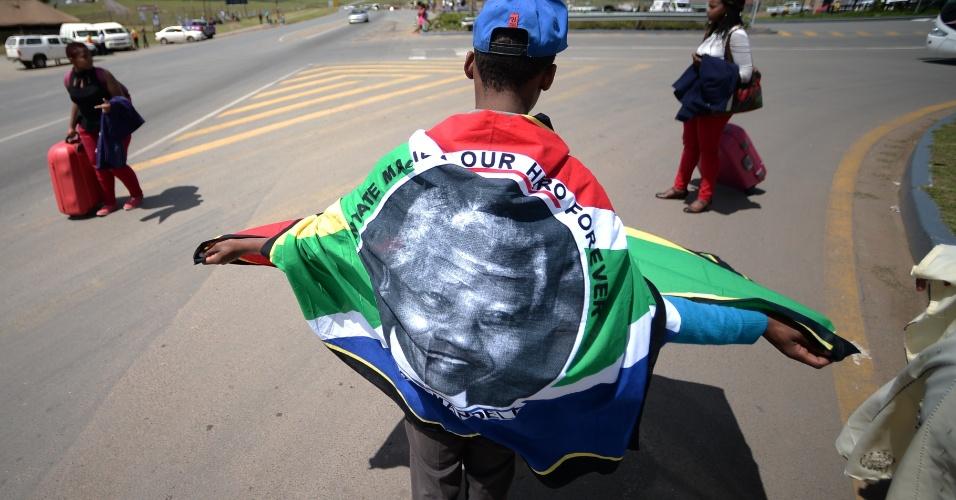 14.dez.2013 - Garoto caminha enrolado com bandeira sul-africana enquanto espera o comboio que transporta o caixão de Nelson Mandela passar por Mthatha, no caminho para Qunu, onde o ex-presidente da África do Sul será enterrado