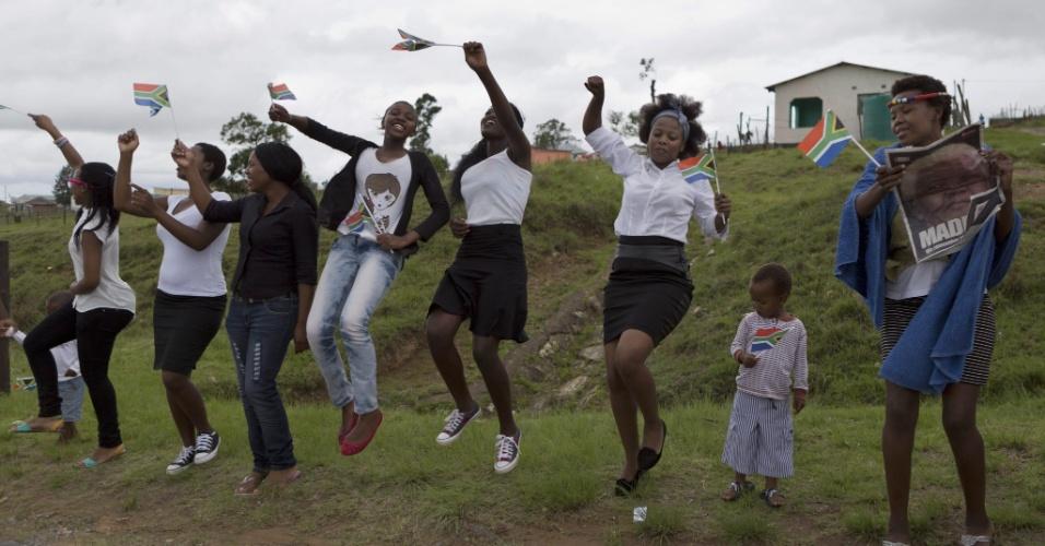 14.dez.2013 - Jovens sul-africanas prestam homenagem durante cortejo fúnebre do corpo de Nelson Mandela pelas ruas de Mthatha