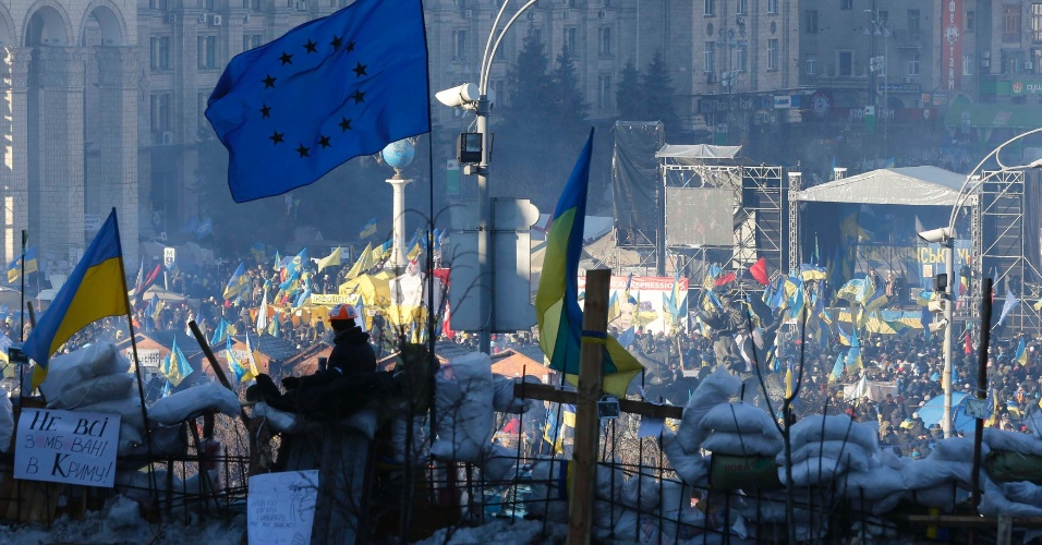 14.dez.2013 - Manifestante ucraniano pró-Europa assiste a protestos de uma barricada na Praça da Independência, em Kiev
