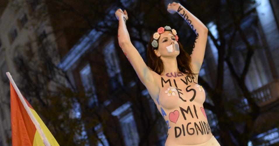14.dez.2013 - Mulher seminua traz no corpo a frase ''Minha voz é minha dignidade'' durante protesto anticapitalista em Madrid, Espanha. Um grupo de manifestantes cercou o congresso na capital do país pedindo por ''democracia social genuína'' e mudanças políticas