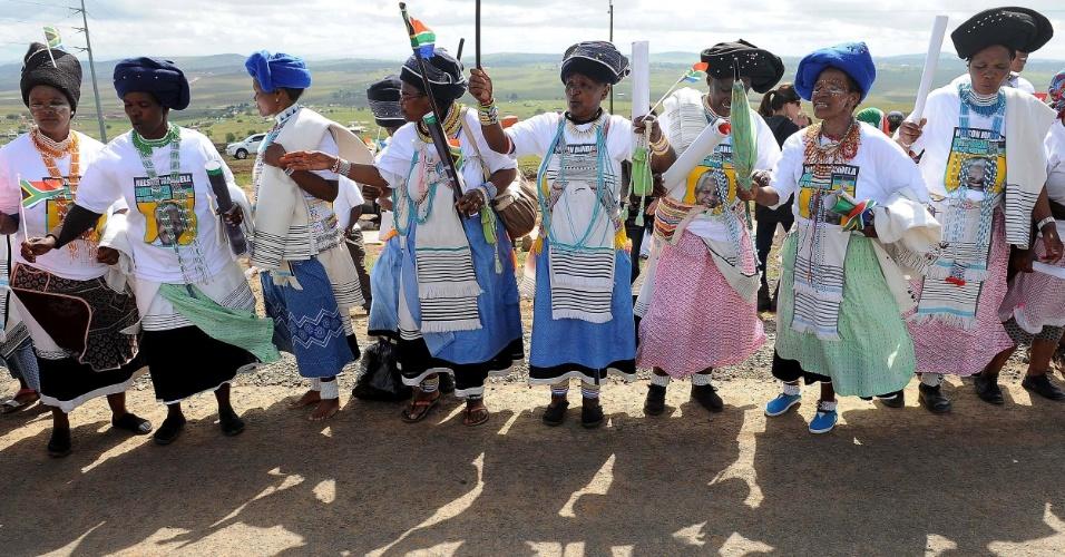 14.dez.2013 - Mulheres dançam durante passagem de cortejo fúnebre com o corpo de Nelson Mandela, que será enterrado na vila de Qunu neste domingo (15)