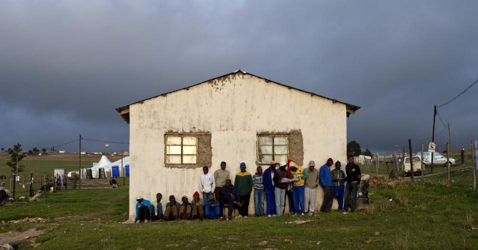 14.dez.2013 - Pessoas aguardam perto da casa onde Nelson Mandela viveu durante a infância na aldeia de Qunu. O corpo do ex-líder sul-africano já chegou ao local; o enterro será neste domingo (15)