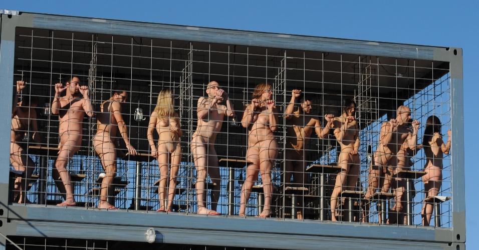 14.dez.2013 - Pessoas ficam nuas dentro de uma jaula como parte de um projeto do artista alemão Wolfgang Flatz, durante festival de inverno em Munique, na Alemanha. De acordo com Flatz, a ideia da ação é protestar contra o crescimento de animais em cativeiro E pedir melhores condições aos animais