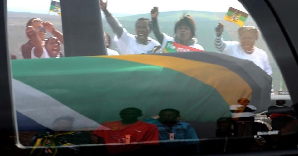 14.dez.2013 - Pessoas prestam últimas homenagens a Nelson Mandela, durante passagem do cortejo fúnebre que leva o corpo do líder sul-africano a Qunu, a 900 quilômetros de distância de Johannesburgo