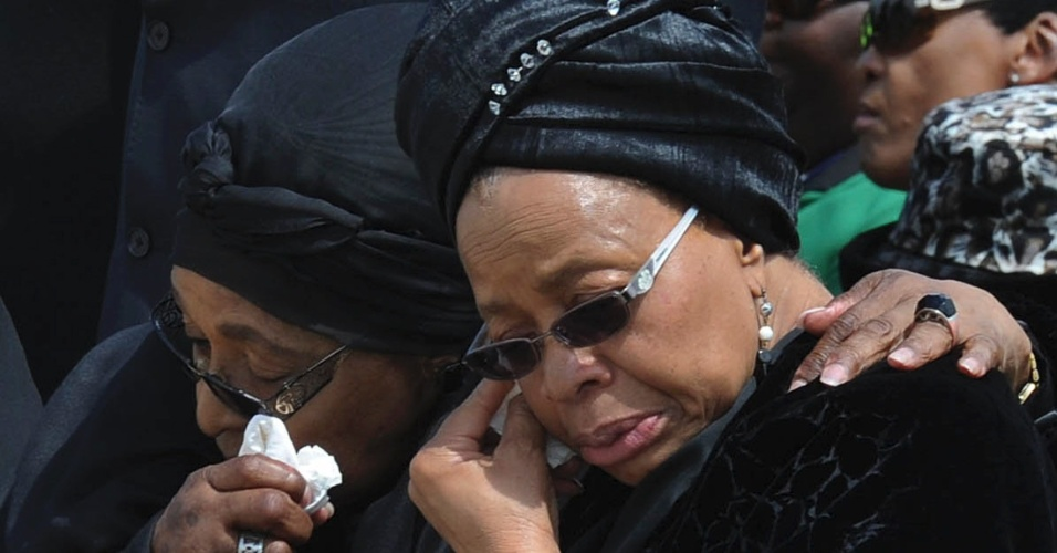 14.dez.2013 - Winnie Mandela (esq.), ex-mulher de Nelson Mandela, e Graça Machel, viúva do ex-presidente sul-africano, choram durante a chegada do caixão no aeroporto de Mthatha. O corpo de Nelson Mandela será enterrado na vila de Qunu neste domingo (15)