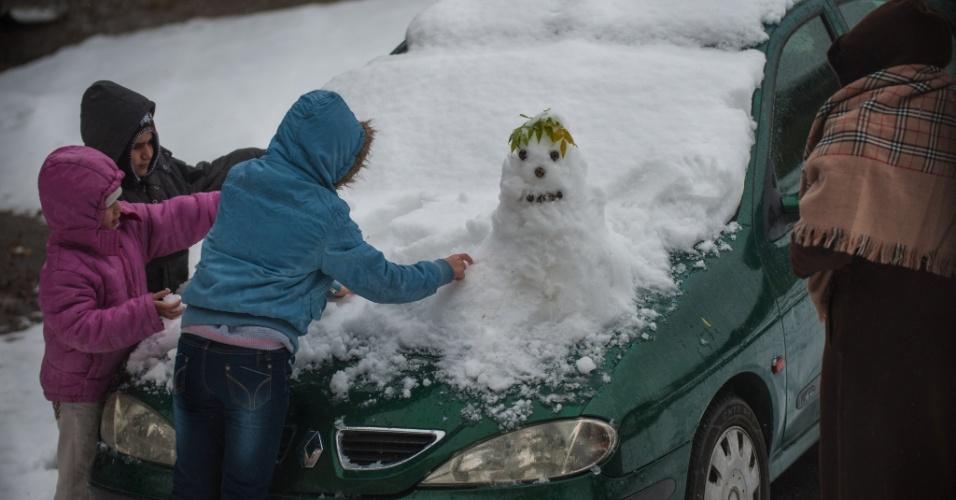 14.dez.2013 - Crianças fazem boneco de neve em carro em Jerusalém