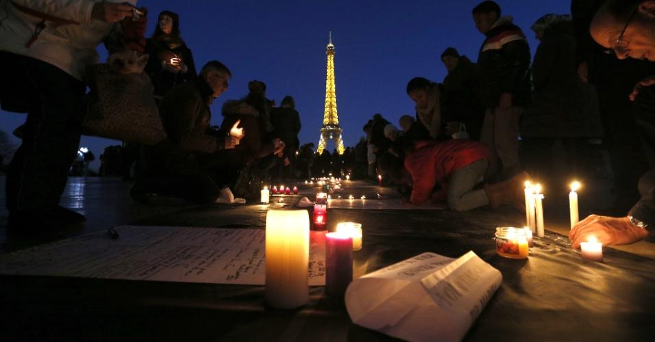 15.dez.2013 - A Torre Eiffel aparece ao fundo enquanto pessoas acendem velas em um tributo em Paris, França, ao ex-presidente sul-africano Nelson Mandela, que morreu no último dia 5 de dezembro aos 95 anos