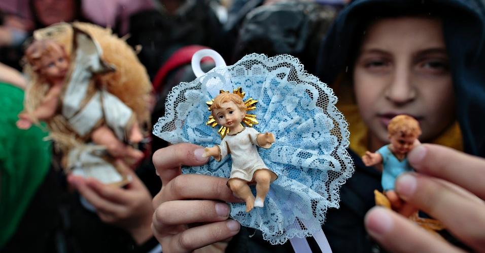 15.dez.2013 - Criança segura escultura do menino Jesus durante oração do Angelus, proferida pelo Papa Francisco,  na Praça de São Pedro (Vaticano)