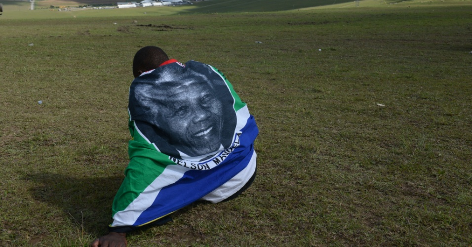 15.dez.2013 - Enrolado em uma bandeira sul-africana, o jovem Mnikelo Ndagankulu assiste à distância ao funeral de Nelson Mandela em Qunu